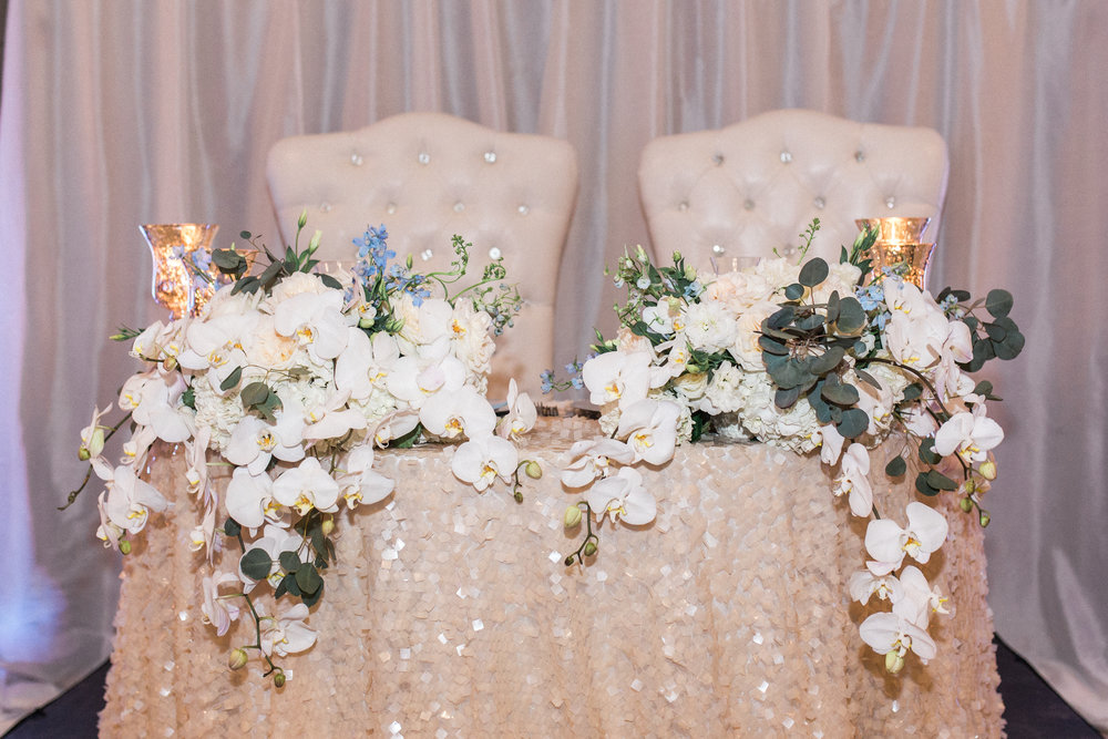 sweetheart table with draped orchards and sequin tablecloth