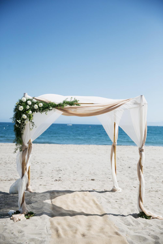 floral-adorned chuppah on the beach