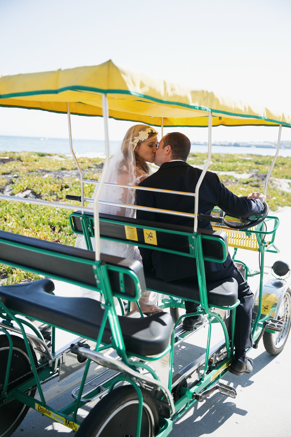 bride and groom ride along the beach