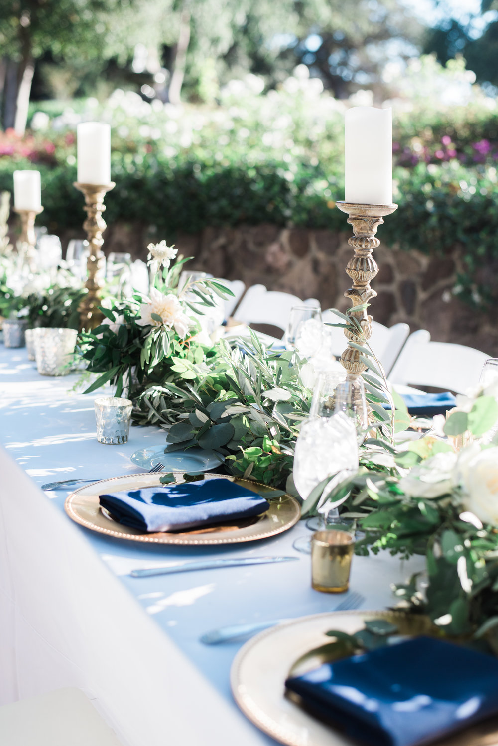 reception table with lush greenery and pillar candles