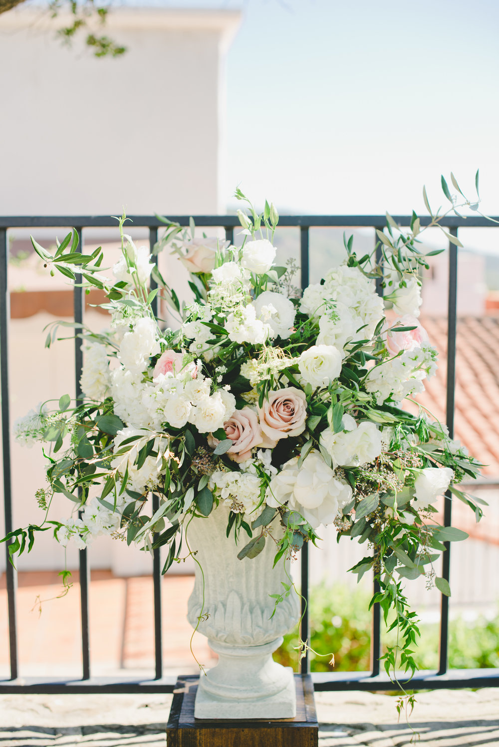large white and blush floral arrangement in stone urn