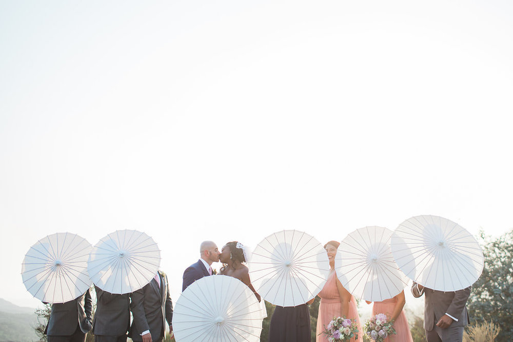 bridal party pose with paper umbrellas