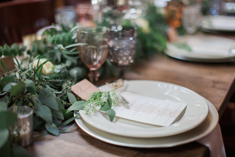 tablescape with eucalyptus garland and smoked vintage glassware