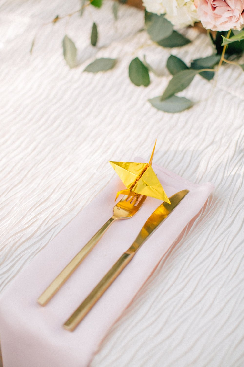 golden origami crane at place setting
