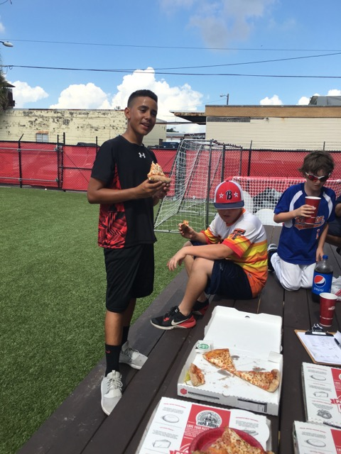 boys eating pizza at the picnic table