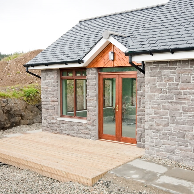 Traditional stone cladding. Hardwood timber windows and doors leading out onto a wooden decking.