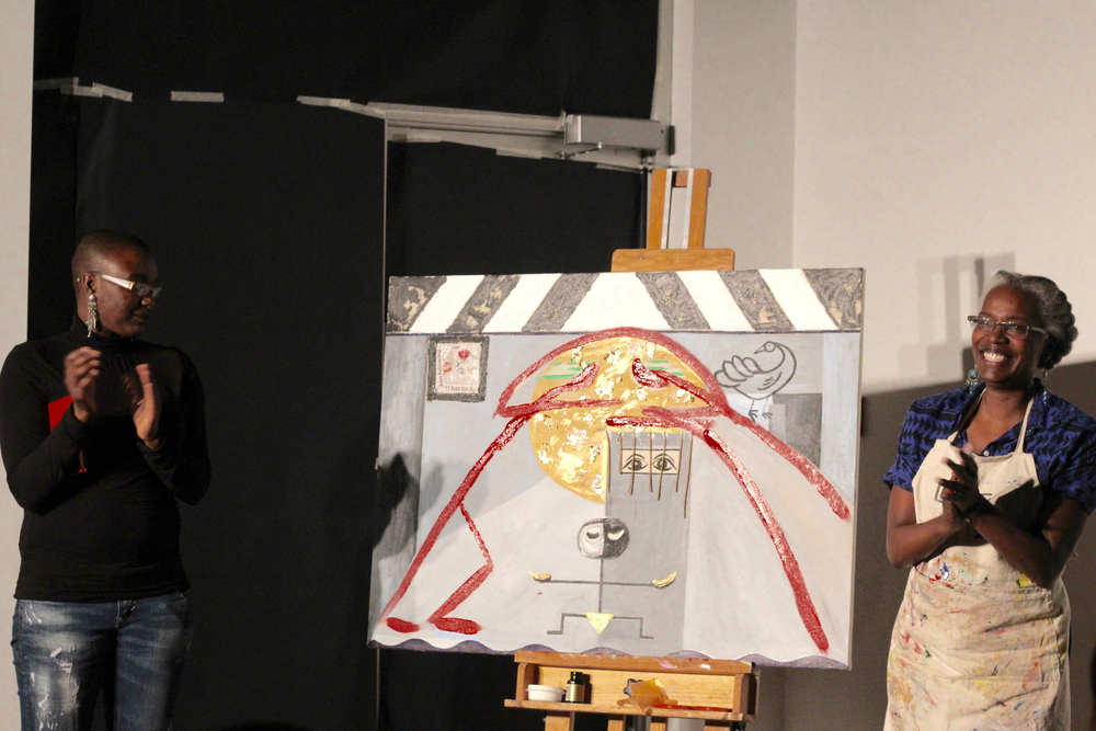 Elsa Robinson (right) and daughter Shima Robinson (left) proudly stand beside a finished painting that came out of their collaborative performance.