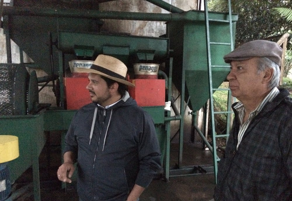 Josué Morales (left), our partner at TG Lab, stands with Don Carlos, the manager of Fátima, in front of the farm's tiny onsite mill.