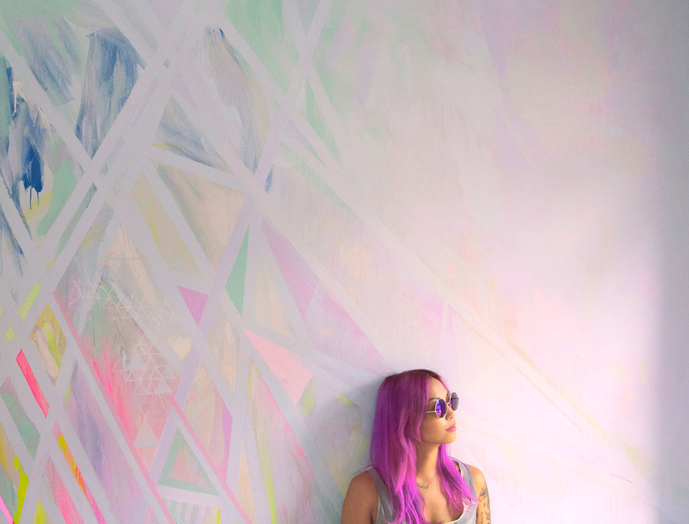Abstract geometric prism wall art mural painted in pastel colors located in NYC bedroom, styled interior design shoot, model leans against wall and has magenta pink dyed hair and arm tattoos.