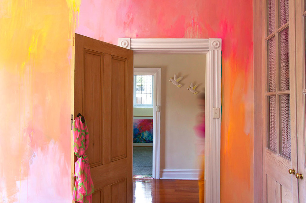 Gorgeous, bright bedroom idea styled with abstract painted mural in hot pink, orange and yellow with white washed closet.