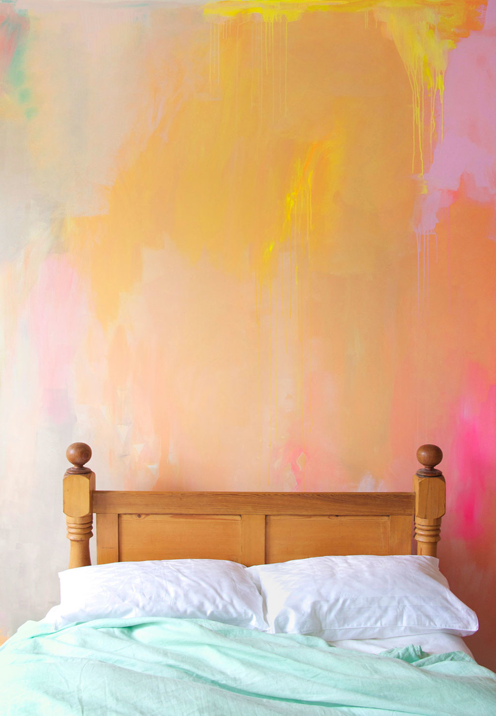 Bright, happy styled bedroom with painted abstract mural in earthy summer colors of peach, coral, yellow and pink, featuring mint bed linen and a messily styled bed.