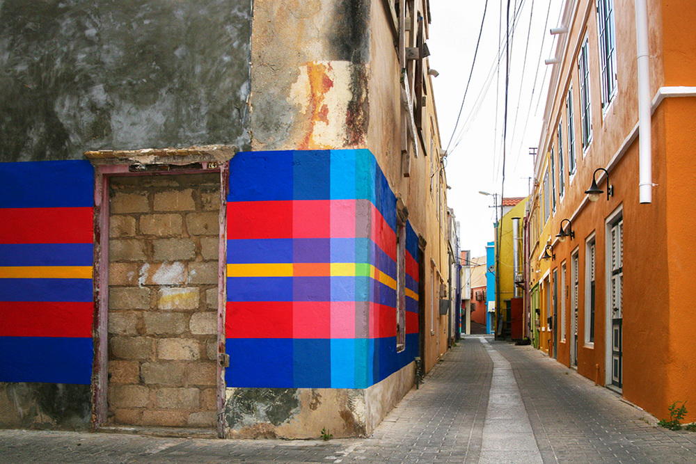 Haas & Hahn community mural project in Curacao, workshop part of Favela Painting Academy, design features brightly colored geometric squares that wrap around the building like woven fabric.