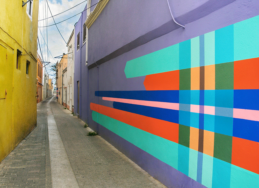 Haas & Hahn community mural project in Curacao, workshop part of Favela Painting Academy, design features brightly colored geometric squares and shapes that wrap around the building like woven fabric.