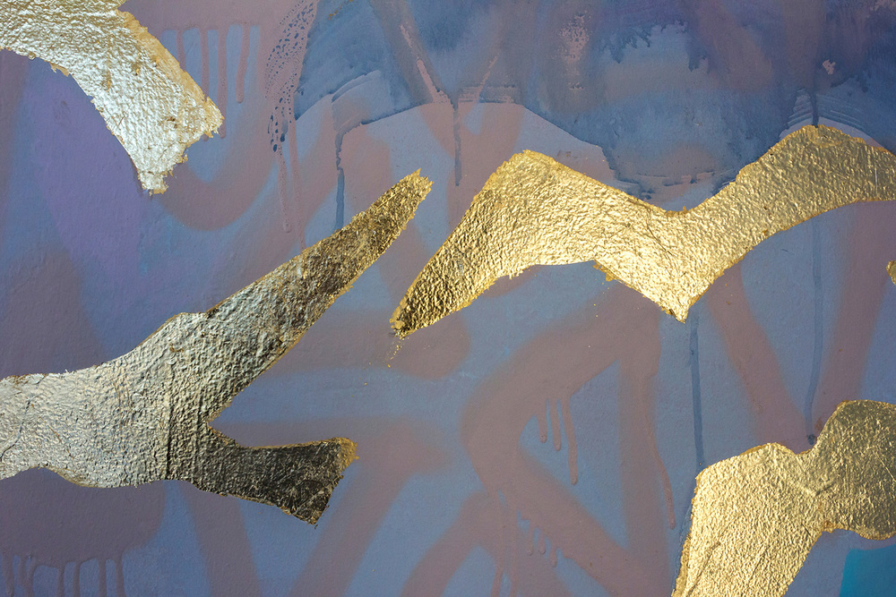 Close up abstract painted mural with painted drips and metallic gold leaf birds flying, spray painted geometric shapes feature in the background.