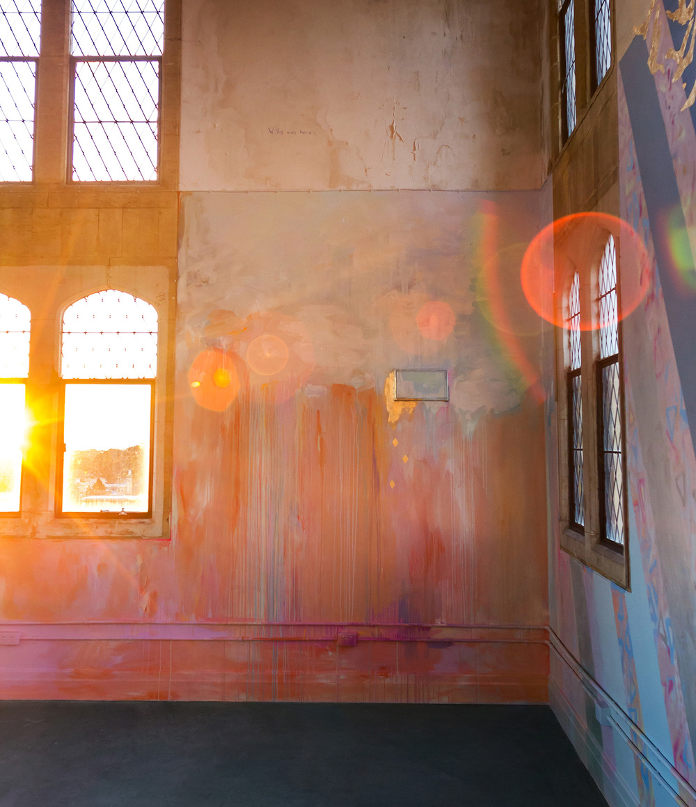 Lens flare creates light rainbow patterns as setting sun streams warmly through window, bounces light on the abstract mural.