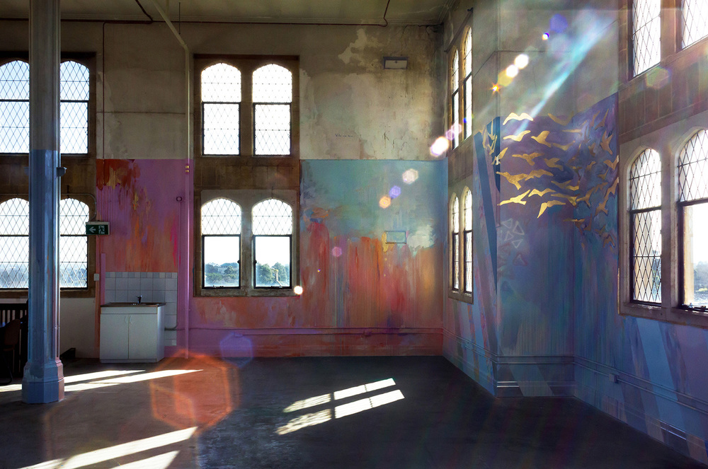 Lens flare creates light rainbow patterns like jewels, bouncing light on the abstract mural, painted in pastel colours with gold leaf birds flying out the window.