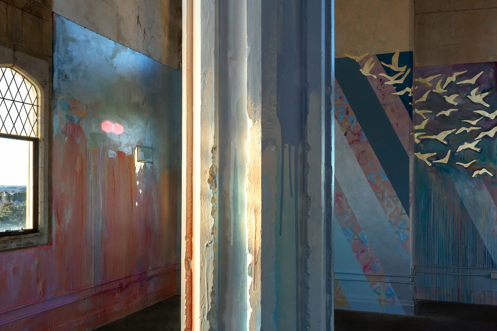 Large scale abstract mural with rainbow stripes in warehouse like tower, features gold leaf metallic birds flying out of the window, round arch windows, pillars and concrete floor.