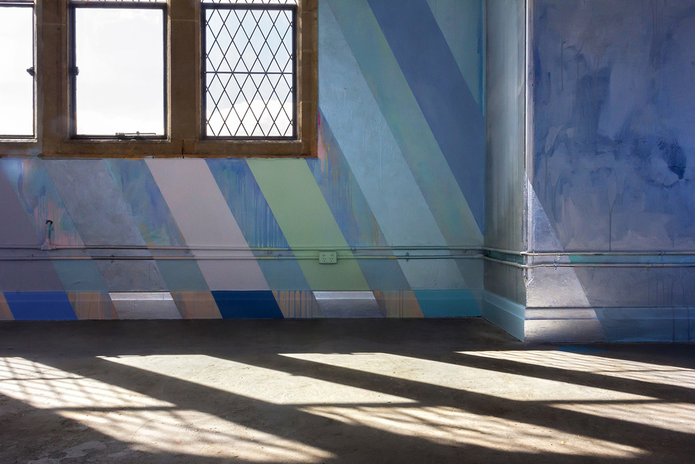 Large scale abstract contemporary mural with rainbow stripes in warehouse like tower, features reflected light patterns on the concrete floor.
