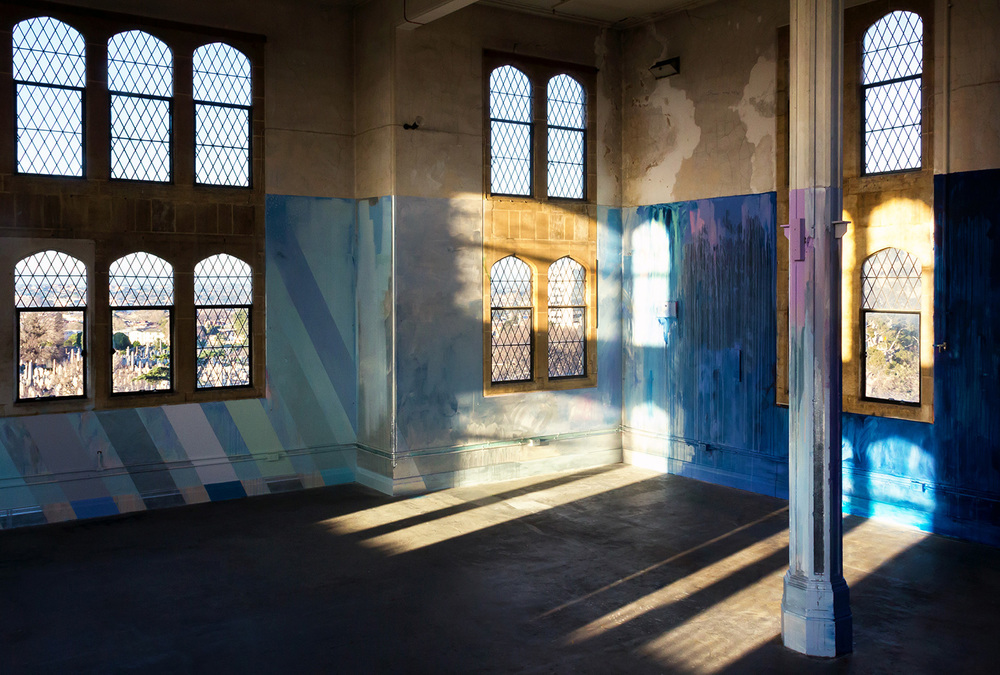 Large scale abstract mural in shades of dark blue and metallic paint, reflected patterns of light project ghostly patterns onto the floor and walls.
