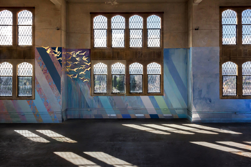 Large scale abstract mural with rainbow stripes in tower, features gold leaf metallic birds flying out of the window and reflected patterns of light on the floor.