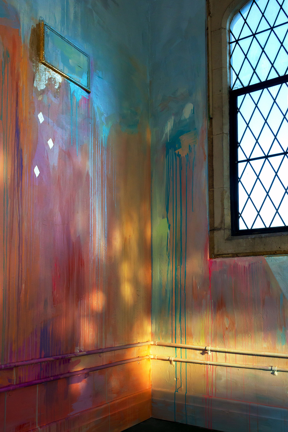 Large scale abstract mural with rainbow stripes in warehouse like tower, features gold leaf metallic birds flying out of the window, round arch windows, pillars and concrete floor, reflections of light looks like fire and fairy lights.