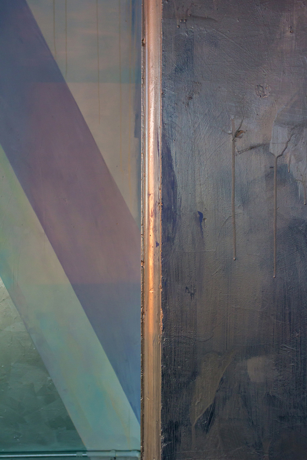 Detail of abstract contemporary painting, part of a large scale mural painted in a warehouse like tower, features geometric silver leaf shapes and metallic silver paint reflecting light.