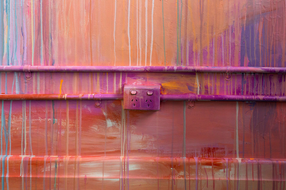 Close up power socket, part of larger abstract painted mural, brush strokes and drips of bright energetic color are featured.