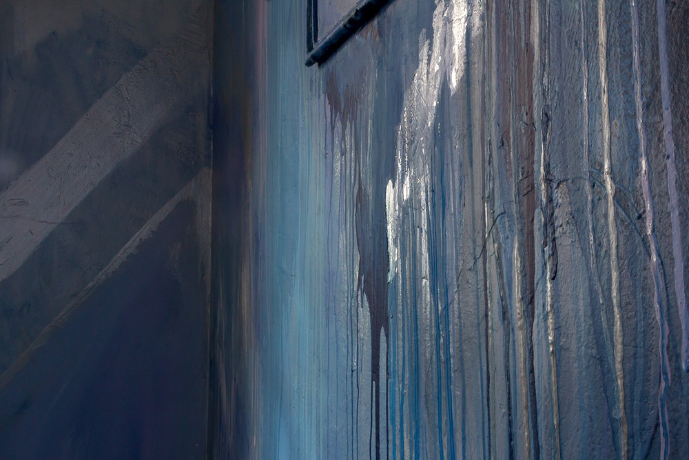 Detail of abstract contemporary painting, part of a large scale mural painted in a warehouse like tower, features geometric shapes and metallic silver paint.