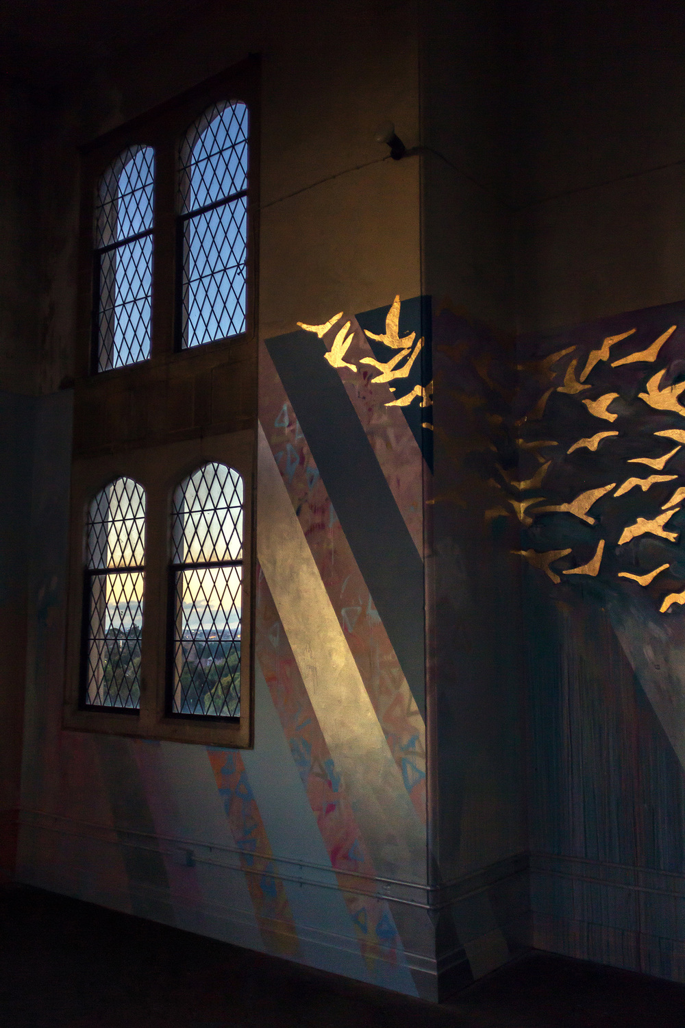 Majestic, religious church like interior, part of a large scale abstract mural, gold leaf birds fly out the window while sunlight projects glowing light onto the wall.