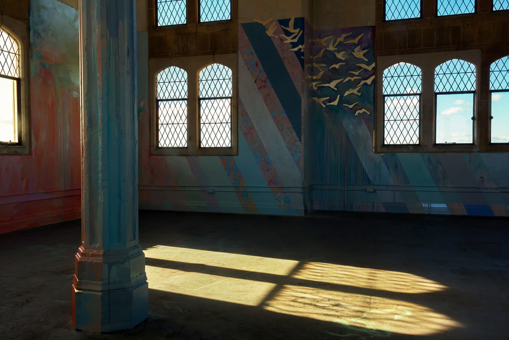 Majestic, religious church like interior, part of a large scale abstract mural, gold leaf birds fly out the window while sunlight projects ethereal patterns onto the floor.