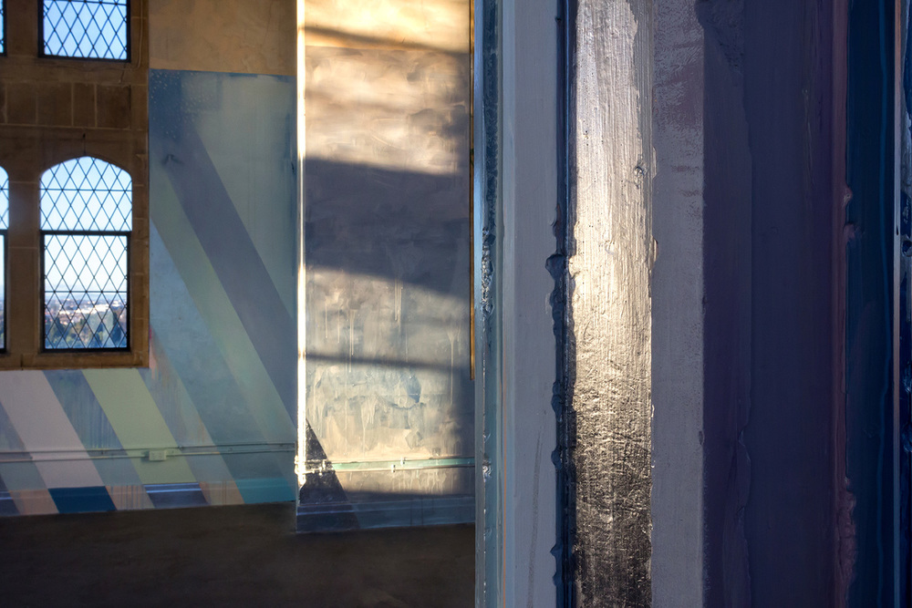 Detail of abstract contemporary painting, part of a large scale mural painted in a warehouse like tower, features geometric shapes and metallic silver paint reflecting light.