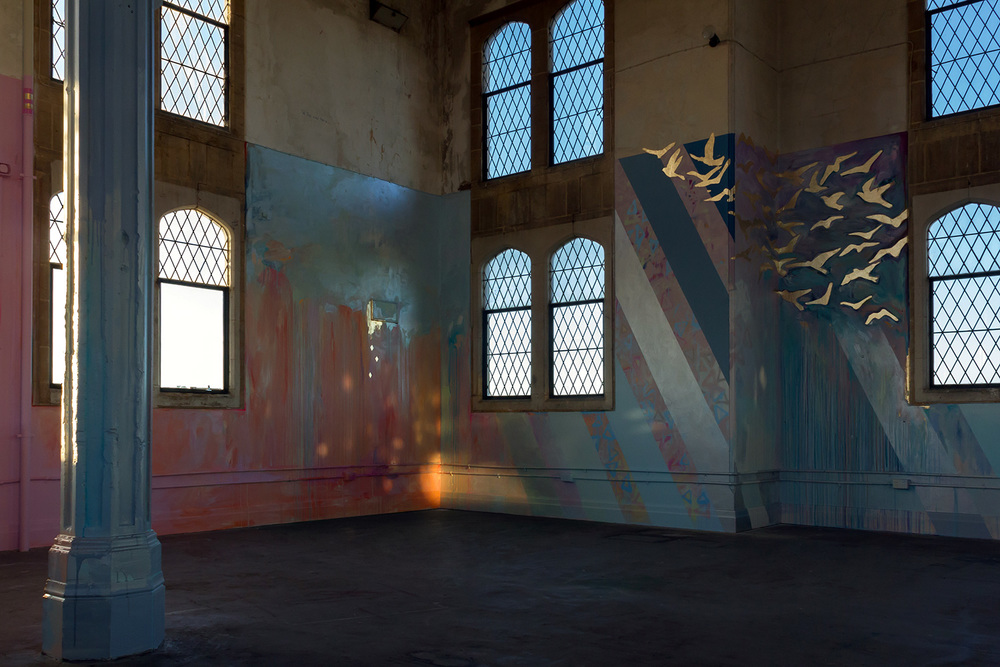 Large scale abstract mural with rainbow stripes in warehouse like tower, features gold leaf metallic birds flying out of the window, round arch windows, pillars and concrete floor, reflections of light looks like fire.