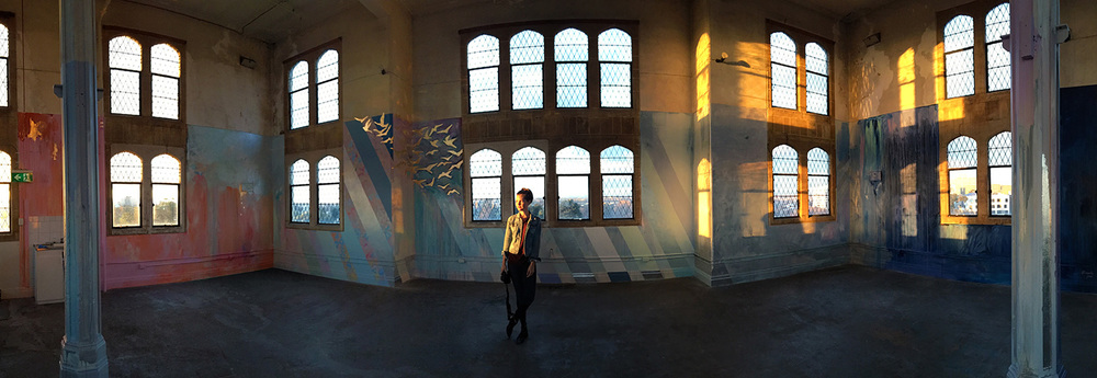 Panorama of large scale abstract mural with rainbow stripes in warehouse like tower, features gold leaf metallic birds flying out of the window, round arch windows, pillars and concrete floor.