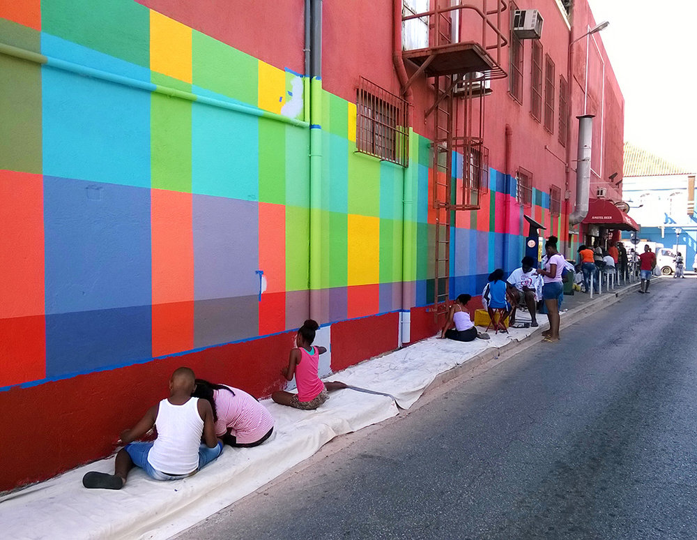 Community art mural project run by Haas & Hahn, kids help paint the design which features brightly colored geometric squares that wrap around the building like woven fabric.