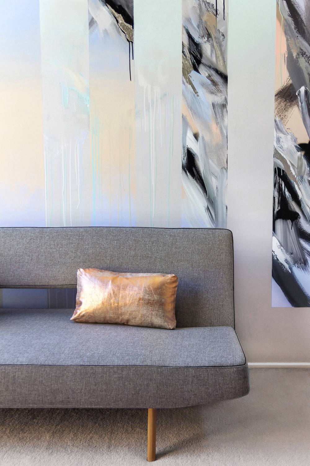 Abstract mural in living room painted with black and white and gradient, beautifully styled with a modern grey couch by Innovation Living and metallic copper cushion.