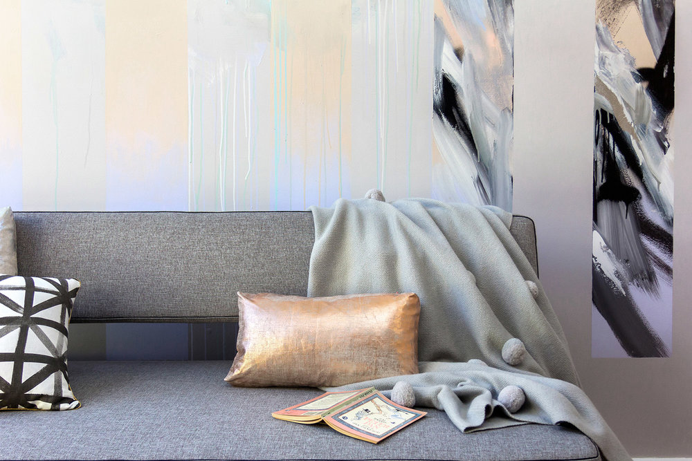 Abstract mural in living room with silver leaf and gradient, beautifully styled with a couch by Innovation Living, Bonnie and Neil cushion, metallic cushion and pom pom blanket by Kip&Co.