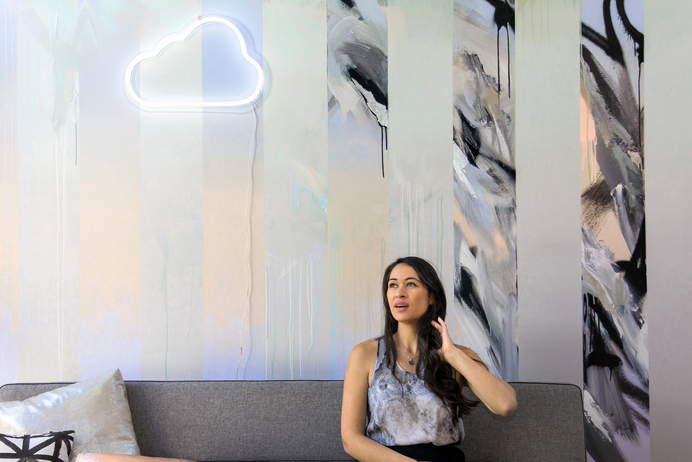 Model sits on grey modern couch and gazes into the distance, behind her is an abstract mural painted in pastels and silver leaf, beautifully styled with an LED neon cloud sign.