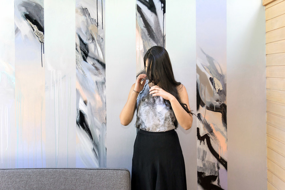 Gorgeous model with long wavy black hair wears a marble silk top and high waist black skirt, she hides her face with her hands and stands in front of an abstract wall art mural.