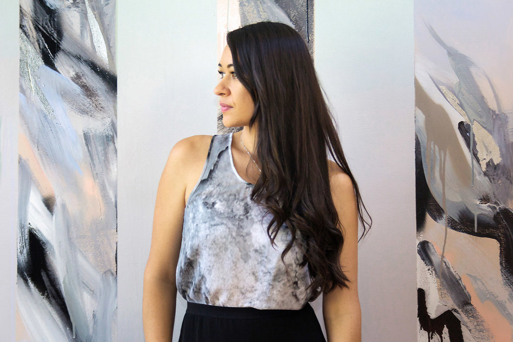 Gorgeous model with long wavy black hair and tanned skin wears a marble silk top and modern high waist skirt, she stands in front of an abstract wall mural that is contemporary and features gradients.
