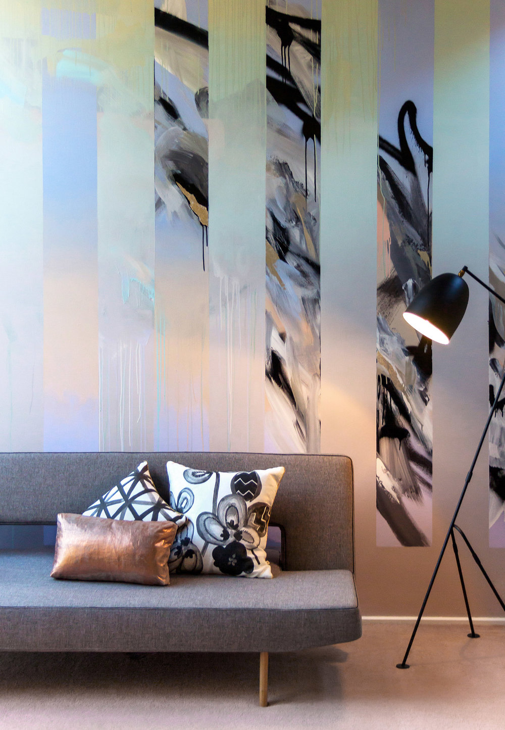 Abstract mural in living room painted in pastels featuring drips, gradient and silver leaf, beautifully styled with a grey sofa bed by Innovation Living, metallic copper cushion, black & white floral Bonnie & Neil cushion, contemporary black lamp by Beacon Lighting.