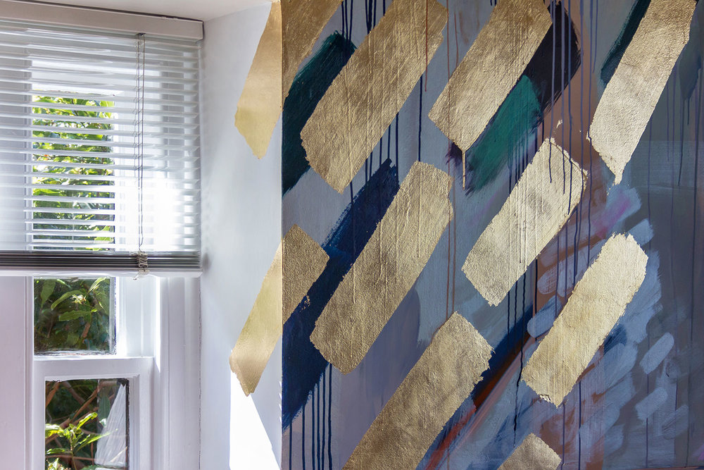 Close up of modern abstract painted wall mural in kitchen, has gold leaf geometric shapes and reflective finishes.