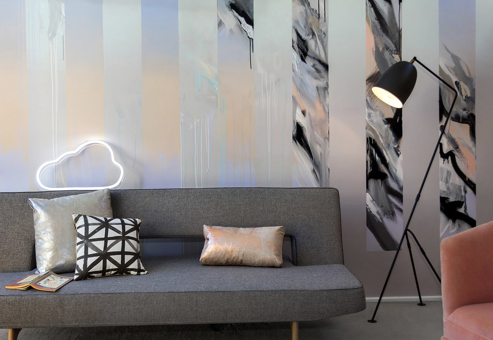 Abstract mural in living room painted in pastels and silver leaf, beautifully styled with a grey sofa bed by Innovation Living, metallic silver and copper cushions, black & white Bonnie & Neil cushion, contemporary black lamp and LED neon cloud sign.