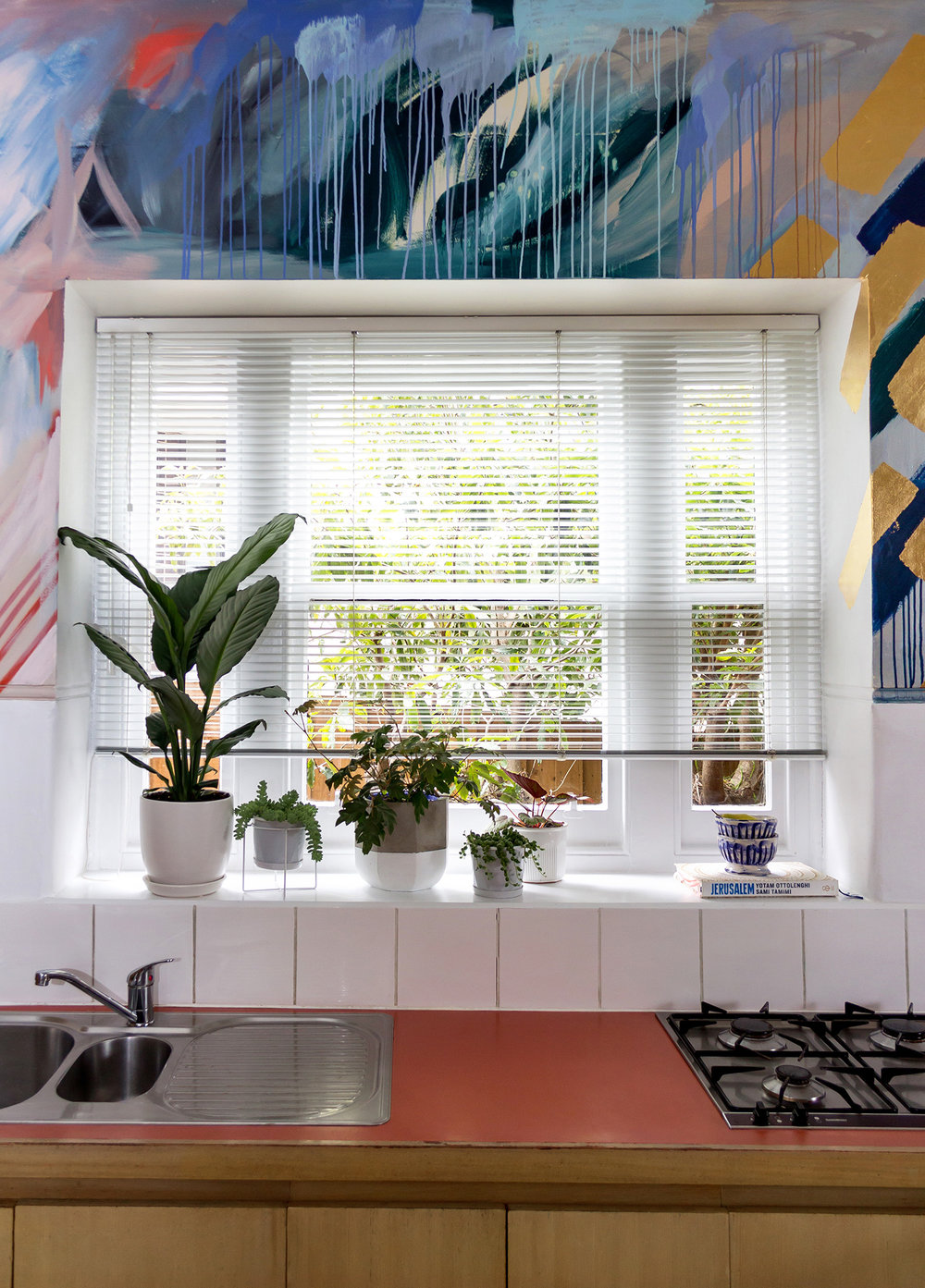 Modern, clean styled kitchen featuring gorgeous abstract mural with gold leaf geometric shapes, contemporary and fresh feel with green plants on windowsill.