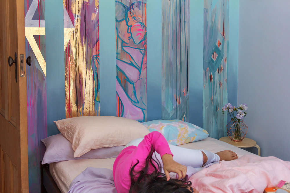 Model lies on bed with pastel linen sheets by Kip & Co, playfully styled bedroom with romantic abstract mural of two people dancing and in love.