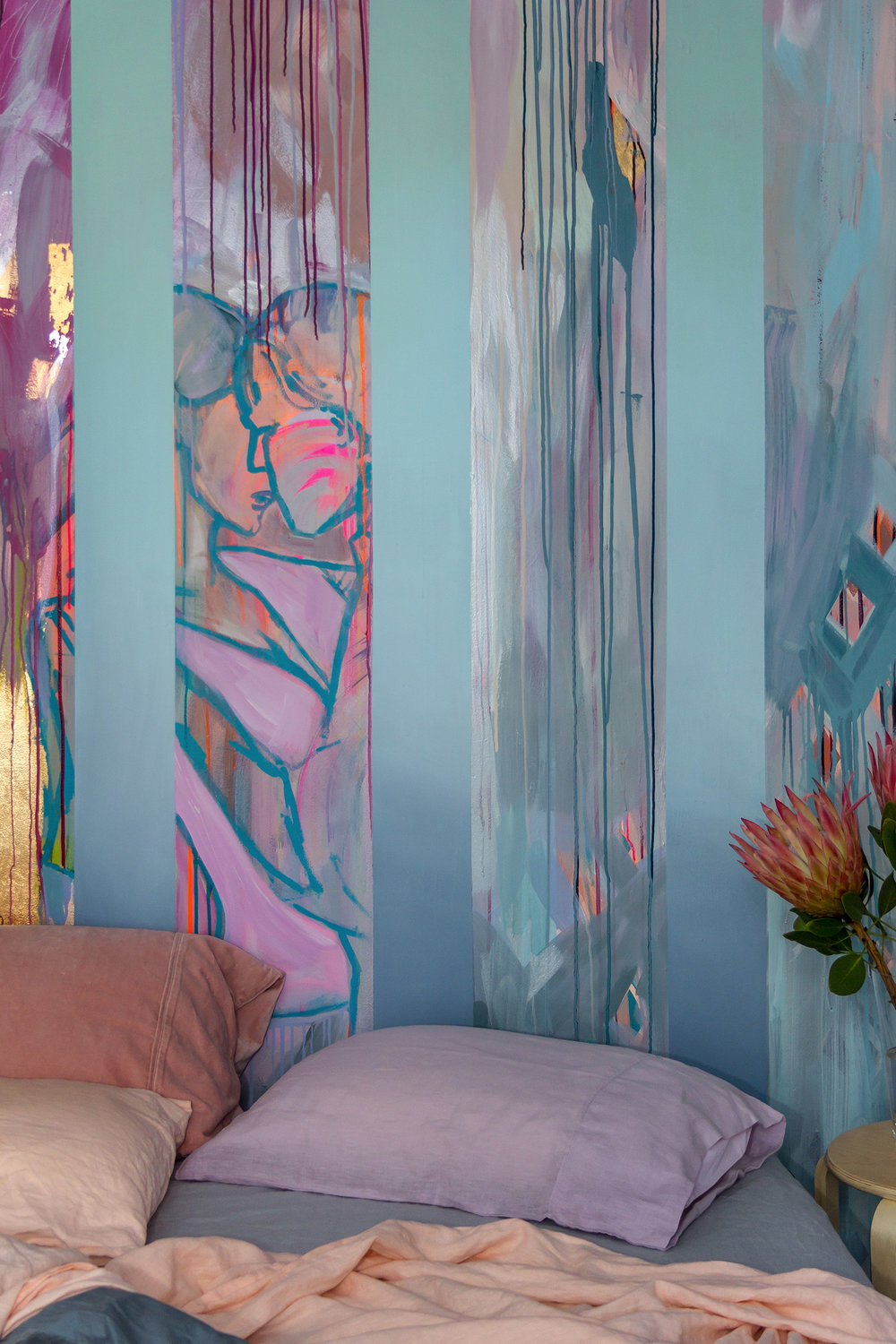 Romantic and playfully styled bedroom with abstract mural of two people dancing and in love, featuring pastel bed linen in peach, pink, lavender and blue by Kip & Co and King Protea flowers on bedside table.