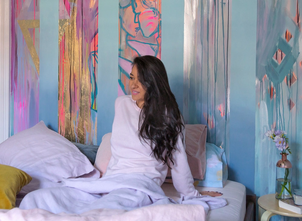 Model in bed with long wavy black bed hair in a romantic and playfully styled bedroom with abstract mural of two people dancing and in love.