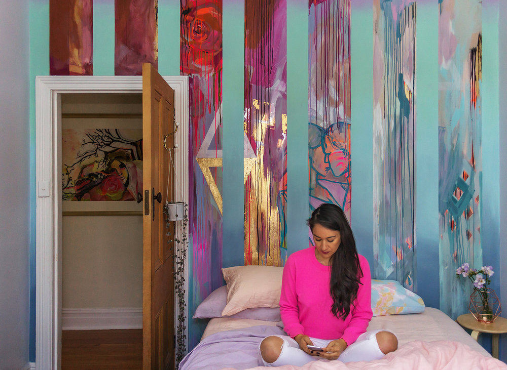 Model sits on bed with pastel linen sheets by Kip & Co texting her boyfriend, playfully styled bedroom with romantic abstract mural of two people dancing and in love, featuring floral landscape art print and chain of hearts plant.