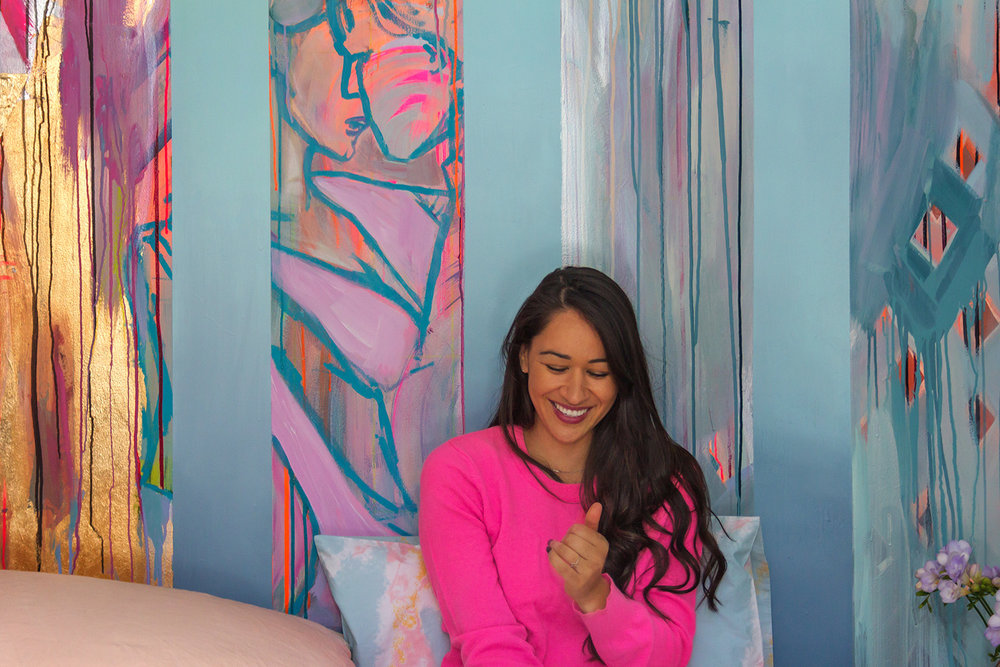 Model, girl in love, laughing and smiling warmly while sitting on bed with pastel linen sheets by Kip & Co, playfully styled bedroom with romantic abstract mural of two people dancing and in love.