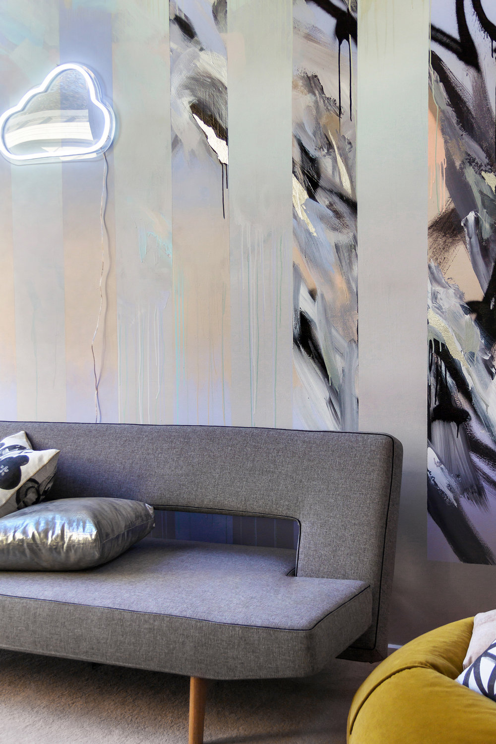 Abstract mural in living room painted in pastels featuring drips, gradient and silver leaf, beautifully styled with a grey sofa bed by Innovation Living, metallic silver cushion and mustard green velvet bean bag by Kip & Co.