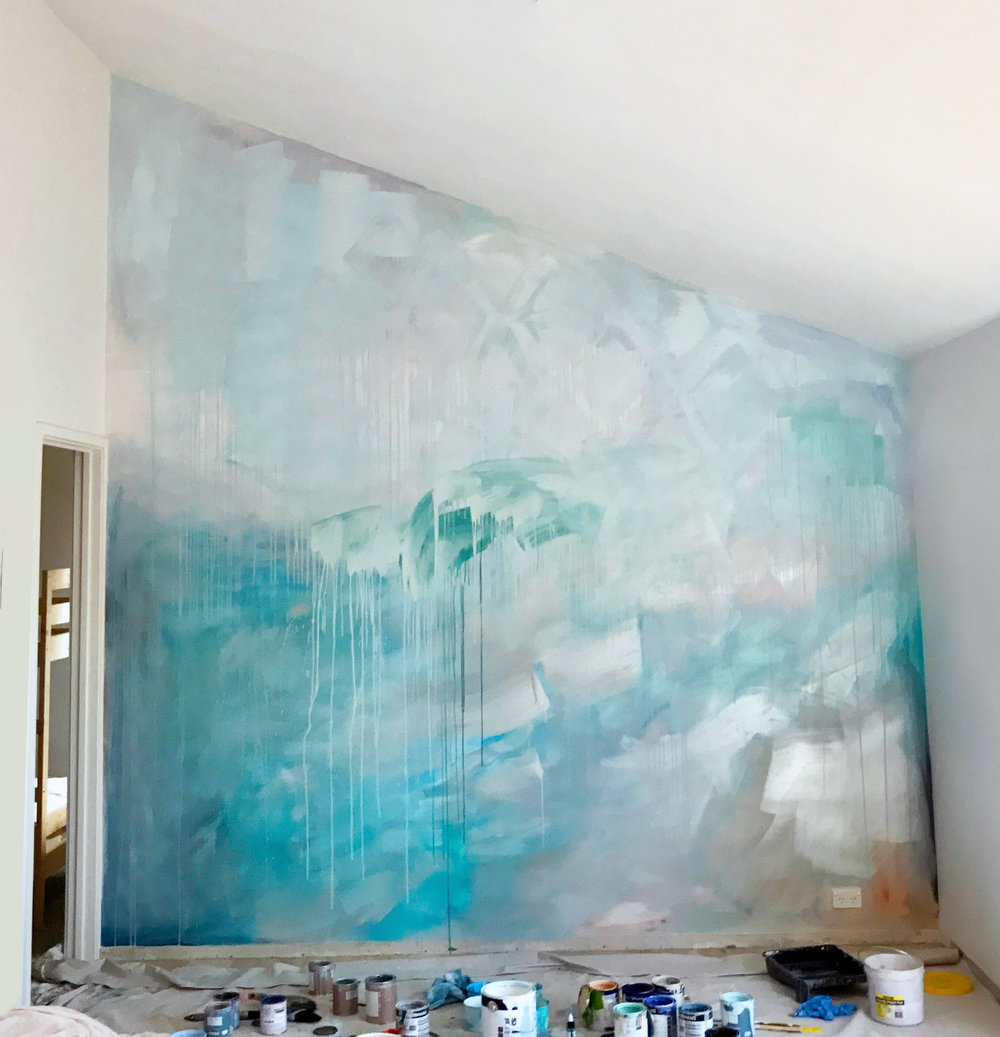Artist Camille Javal work in progress contemporary abstract ocean water mural in pastel blue, green and metallic paint, featuring a wave, drips and geometric shapes, the artwork has movement and reflects light in the living room.